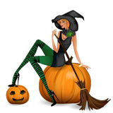 Beauty witch sitting on a pumpkin on Halloween Royalty Free Stock Photography