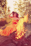 Beauty witch in the woods near the fire. Magic woman celebrating Royalty Free Stock Images