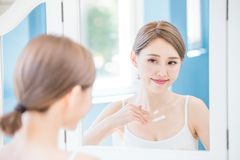 Woman apply cream with neck. Beauty woman apply cream with neck at home stock images
