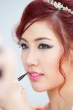 Beauty woman applying lipstick on lips with brush. Stock Photos