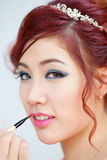 Beauty woman applying lipstick on lips with brush. Royalty Free Stock Images