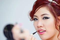 Beauty woman applying lipstick on lips with brush. Stock Photo