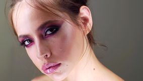 Beauty woman is applying make up on her face. Portrait of beautiful young female with smooth skin and fresh makeup. stock footage