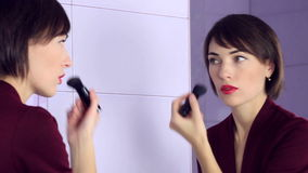 Beauty woman applying makeup. Beautiful girl looking in the mirror and applying cosmetic with big brush. stock video footage