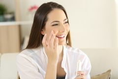 Beauty woman applying moisturizer cream on the face. Portrait of a beauty woman applying moisturizer cream on the face sitting on a couch in the living room at Royalty Free Stock Images