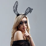 Beauty woman blonde girl with bunny rabbit in studio puts a finger to her lips Royalty Free Stock Images