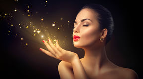 Beauty woman blowing magic dust with golden hearts royalty free stock images