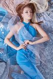 Beauty woman in blue dress on pattern. Sensual beautiful girl in colored fabrics Royalty Free Stock Photography