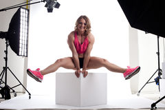 Beauty woman body builder sit on cube in studio Royalty Free Stock Photo