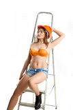 Beauty woman builder sits on a ladder Stock Photo