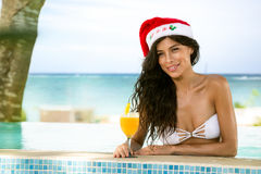 Beauty woman with Christmas hat in swimming pool Stock Images