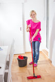 Beauty Woman Cleaning Home. Beauty woman cleaning and mopping floor at home Stock Image