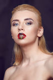 Beauty woman with creative make up red plump lips. Beauty woman with creative make up and red plump lips. Portrait of beautiful young blonde girl with bright Stock Image