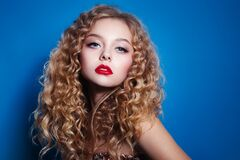 Beauty woman with curly hair afro hairstyle and red lips on classic blue background