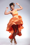 Beauty woman dancing with her dress in the air Stock Images