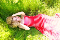 Beauty woman in dress lying on green meadow in grass Royalty Free Stock Images