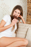 Beauty woman is eating chocolate Royalty Free Stock Photography