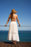 Beauty Woman Enjoying View of Mediterranean Sea. Spain. Young woman on a high-rise balcony overlooking Mediterranean Sea. Backward Royalty Free Stock Images