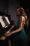 Beauty woman in evening dress playing piano Royalty Free Stock Images