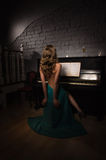Beauty woman in evening dress playing piano Royalty Free Stock Image
