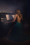 Beauty woman in evening dress playing piano Stock Photo