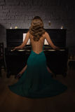 Beauty woman in evening dress playing piano Stock Photography