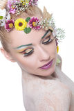 Beauty woman with exptic make up looks down. Closeup of a young beauty woman with exotic make up and floral wreath, looking down. on white background Stock Photos