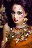 Beauty woman with face art and jewelry from flowers orchids Royalty Free Stock Photo