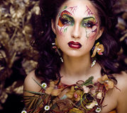 Beauty woman with face art and jewelry from flowers orchids Royalty Free Stock Photos