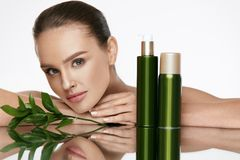 Beauty Woman Face. Beautiful Female With Natural Cosmetics. Beauty Woman Face. Beautiful Female With Natural Organic Cosmetics And Green Leaves On White stock photo