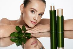 Beauty Woman Face. Beautiful Female With Natural Cosmetics. Beauty Woman Face. Beautiful Female With Natural Organic Cosmetics And Green Leaves On White royalty free stock image