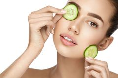 Beauty Woman Face With Fresh Skin In Spa. Female Removing Dark Circles With Cucumber Slices On White Background. High Resolution royalty free stock photo