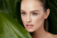 Beauty Woman Face With Healthy Skin And Green Plant royalty free stock photos