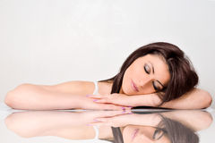 Beauty woman face with mirror reflection. Beautiful face skincare beauty woman lying down with mirror reflection isolated on white background royalty free stock photo