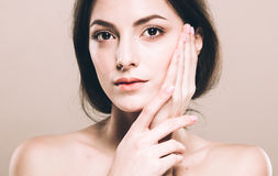 Beauty Woman face Portrait. Beautiful Spa model Girl with Perfect Fresh Clean Skin. Over beige background Royalty Free Stock Photo