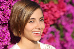 Beauty woman face portrait with a perfect smile and white teeth. With a lot of pink blurred flowers in the background Royalty Free Stock Image