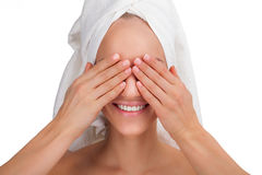 Beauty Woman face Portrait. Smiling girl in a towel close her eyes by hands. Skin Care Concept Isolated on white royalty free stock image
