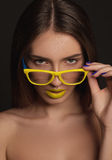 Beauty woman face portrait with yellow lips and yellow glasses. Young model with a perfect skin Stock Photography