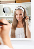 Beauty woman fixing her makeup in the mirror Royalty Free Stock Photography