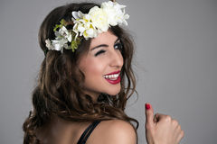Beauty woman with floral tiara turn back and winking at camera with thumbs up. Over gray background Stock Photography