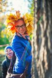 Beauty woman and her son at autumn park Royalty Free Stock Photos