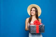 Beauty woman wearing in hat holding paper gift box with Toothy smiling face Isolated blue background. Beauty woman holding paper gift box with Toothy smiling Royalty Free Stock Photos
