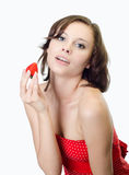 Beauty woman holding strawberry in studio, gray Stock Images