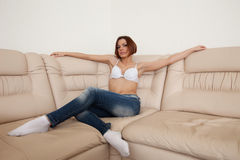 Beauty woman in jeans and white lingerie on sofa Stock Photography