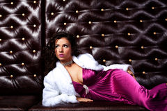 Beauty woman lay on leather sofa Royalty Free Stock Image