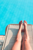 Beauty woman legs laying on beach bed. Near swimming pool Royalty Free Stock Photos
