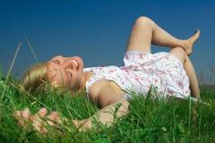 Beauty woman lie on grass. Happy beauty woman lie on green grass under blue sky Stock Photo