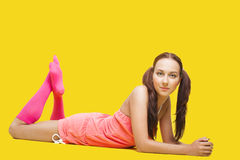 Beauty woman like teenager lay on yellow Royalty Free Stock Photos