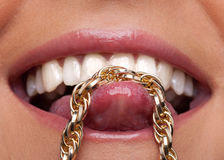 Beauty woman lips and gold chain on tongue Royalty Free Stock Image