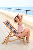 Beauty woman in lounge on veranda on sea Stock Image